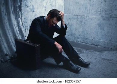 Desperate Businessman lying on the ground and holding his head in a dark tunnel. With room for your text