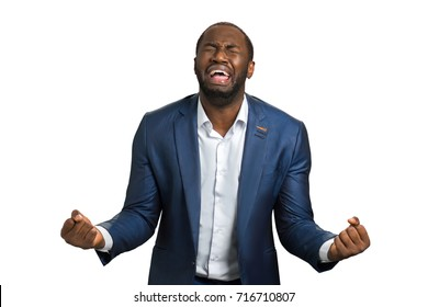Desperate businessman with problems shouting. Frustrated screaming black manager with mouth wide open on white background. Desperate young man shouting with raised fists and closed eyes.