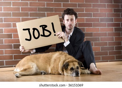 "desperate businessman sits with a dog on the floor and holds a ""Need Job"" sign"