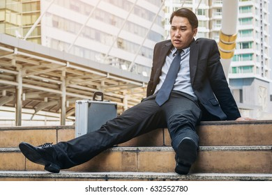 Desperate businessman sitting hopelessly on stair floor. Concept of failure, desperation, unemployment, business depression.