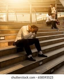 Desperate businessman sitting hopelessly on staircase floor. Concept of failure, desperation, unemployment, business depression.