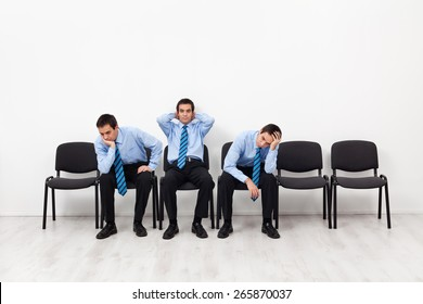 Desperate businessmen sitting on chairs having doubts about the future