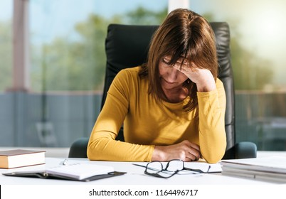 Desperate businesswoman with hand on forehead sitting at desk