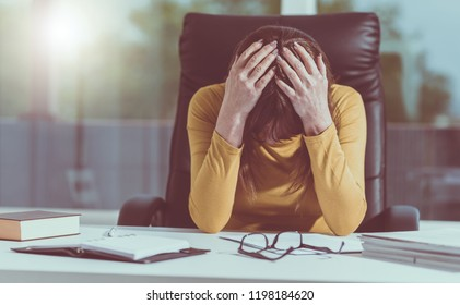 Desperate businesswoman with head in hands sitting at desk, light effect