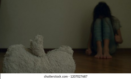 a desperate child in depression sits at the wall of his room, tries to attempt suicide. next to it is an abandoned soft toy