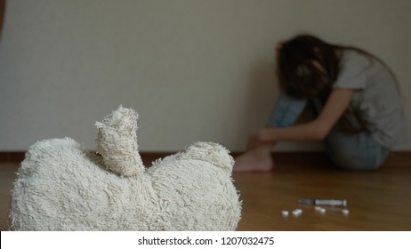 a desperate child in depression sits at the wall of his room, tries to attempt suicide. next to it is an abandoned soft toy.