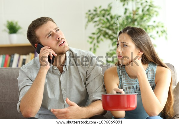 Desperate couple callling to insurance worried about home leaks in the living room
