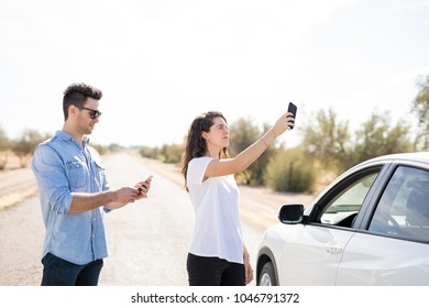 Desperate couple searching mobile phone coverage on road with breakdown car
