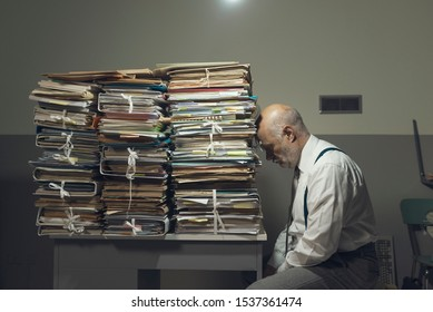 Desperate depressed businessman with lots of paperwork in his messy office at night, he is leaning on a pile of files, bureaucracy and deadlines concept