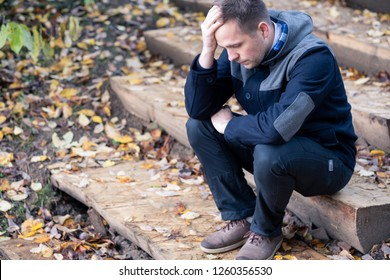 Desperate european man sitting alone on stairs outdoors in autumn. He broke up with his girlfriend. Migraine, education and overworking concept
