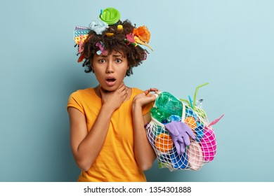 Desperate female environmental activist picks up trash, holds net bag with plastic products, keeps hand on neck, suffers from suffocation, busy on world environment day. Volunteering concept