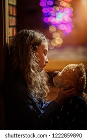 desperate girl in Christmas evening is holding a teddy bear