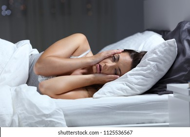 Desperate girl suffering insomnia trying to sleep in a bed at home in the night