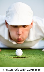 Desperate golfer blowing on golf ball to put in hole, funny golfing cheat - concept