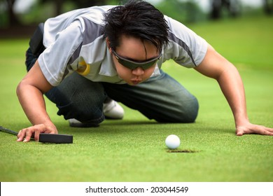 Desperate golfer blowing on golf ball to put in hole, Funny golfing cheat concept