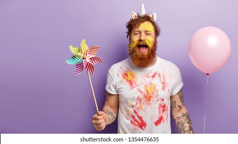 Desperate guy shouts from tiredness, has image of unicorn, being dirty with paints, carries toy windmill and air balloon, dissatisfied with ending of theme party, isolated over lilac wall, free space