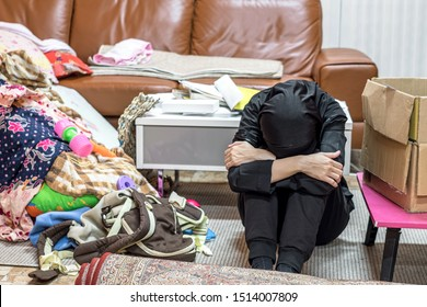 Desperate helpless, frustrated and tired young muslim housewife touching sitting and benting in front of messy area living room in her house.