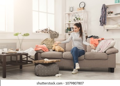 Desperate helpless woman sitting on sofa in messy living room. Young girl surrounded by many stack of clothes. Disorder and mess at home, copy space