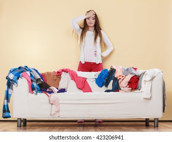 Desperate helpless woman standing behind sofa couch in messy living room with hand on head. Young girl surrounded by many stack of clothes. Disorder and mess at home.