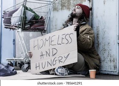 Desperate homeless and hungry tramp with a sign sitting on the street next to a trolley and begging for food and money