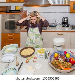 Desperate housewife with hands in the hair for the mess in kitchen she will have to fix