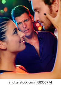 Desperate jealous man looking at flirting couple in discotheque.?