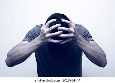 Desperate looking man holding his head with his hands. Depression concept.