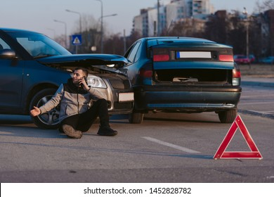 A desperate man is calling for help after car accident on the road, sitting on the asphalt leaning on the car tire