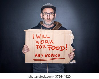 Desperate man holding a cardboard sign Looking for a job in his Hands, will work for food
