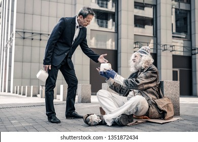 Desperate man. Kind sincere short-haired business man sharing box with food with thankful long-haired homeless