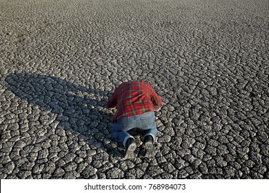 Desperate man kneeling at dry cracked land after drought, natural disaster