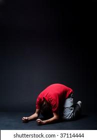 desperate man praying  in darkness