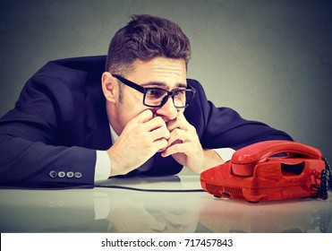 Desperate man waiting for someone to call him