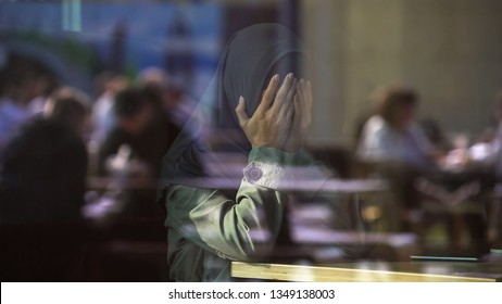 Desperate Muslim female crying in cafe, covering face with hands, loneliness