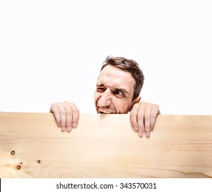 Desperate neighbor. Man with expressive face, looking through wooden fence.
