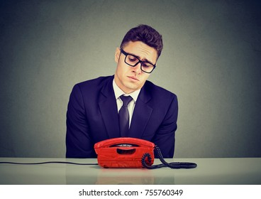 Desperate sad business man waiting for someone to call him