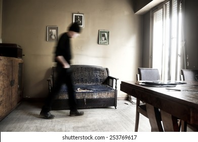 Desperate and skeptical man walking in the living room of an old house