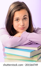 Desperate student girl leaning on stack of books purple background