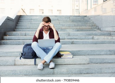 Desperate student sitting on stairs and working on laptop outdoors in university campus. Man raised his hands to his head. Technology, education and remote working concept, copy space