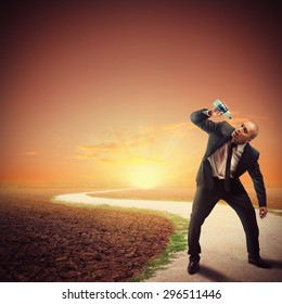 Desperate thirsty businessman in a dry path
