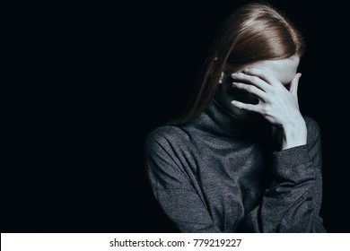 Desperate woman with phobia and anxiety against black background with copy space