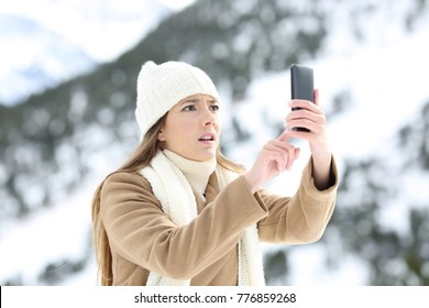 Desperate woman searching mobile phone coverage in winter holidays in a snowy mountain