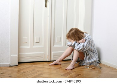Desperate woman sitting on the floor in an empty room.
