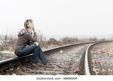 Desperate woman sitting on the railroads.