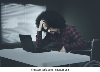 Desperate young african man working with laptop while sitting on wheelchair in the office