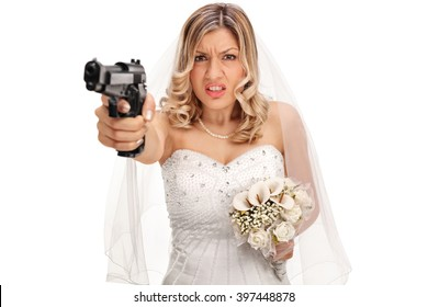 Desperate young bride pointing a gun towards the camera isolated on white background