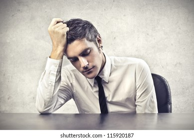 Desperate young businessman leaning on a desk