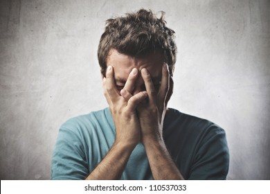 Desperate young man crying in his hands