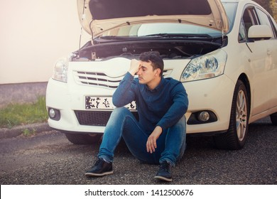 Desperate young man driver seated on the asphalt ground in front of his car open hood. Vehicle breakdown concept. Guy motorist has problems with automobile, human emotions.