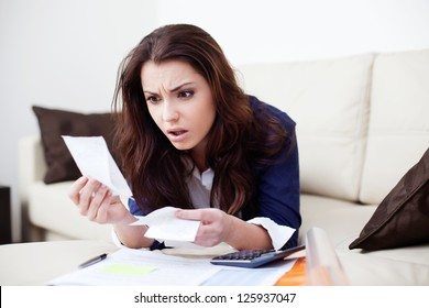Desperate young woman calculating bills in living room